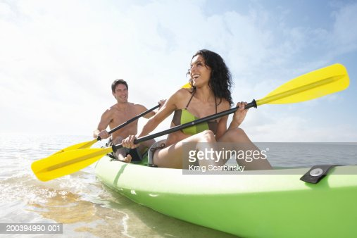 Young couple paddling canoe in bay, smiling : Stock Photo