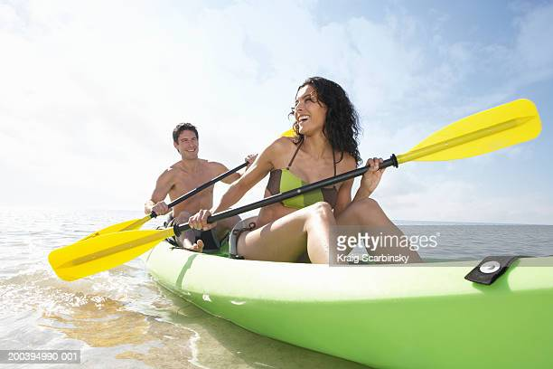 Young couple paddling canoe in bay, smiling