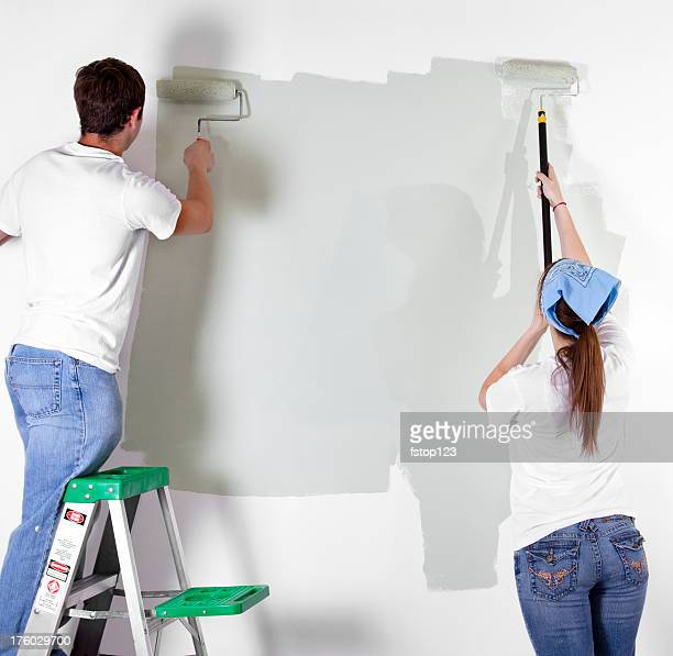 Young couple paint wall in home. DIY, home improvements.