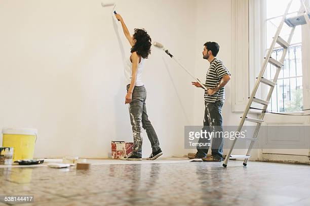 Young couple painting their apartment.
