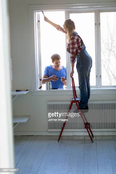 Young couple painting windows, Stockholm, Sweden