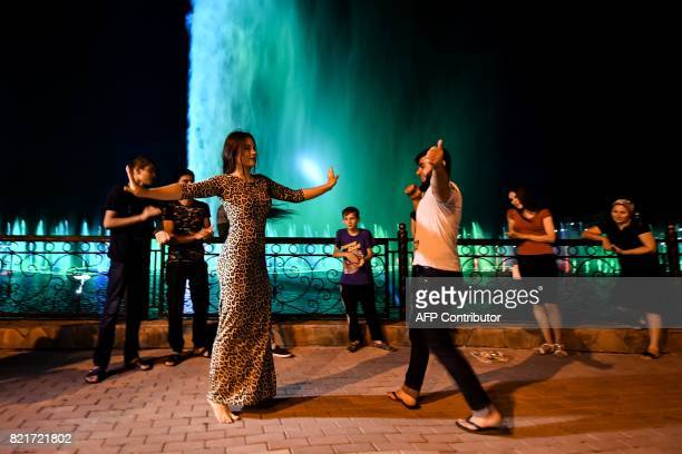 A young couple perform a traditional dance on the bank of Grozny sea in front of coloured fountains in Grozny late on July 24 2017 / AFP PHOTO /...
