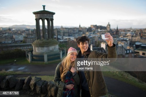 A young couple photograph themselves on Calton Hill with the background of the city of Edinburgh, capital of Scotland