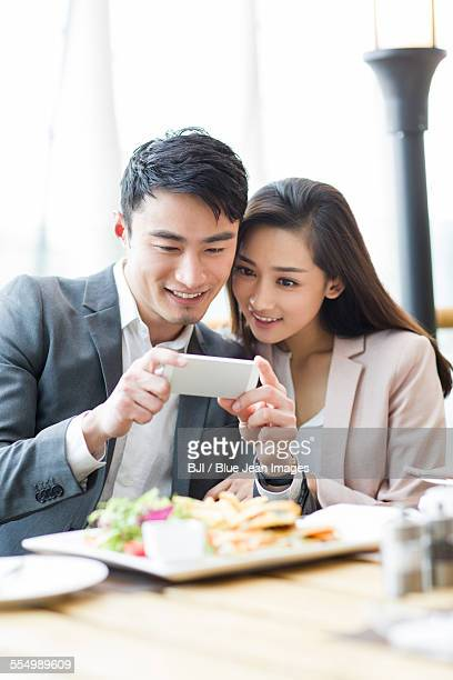 Young couple photographing in restaurant