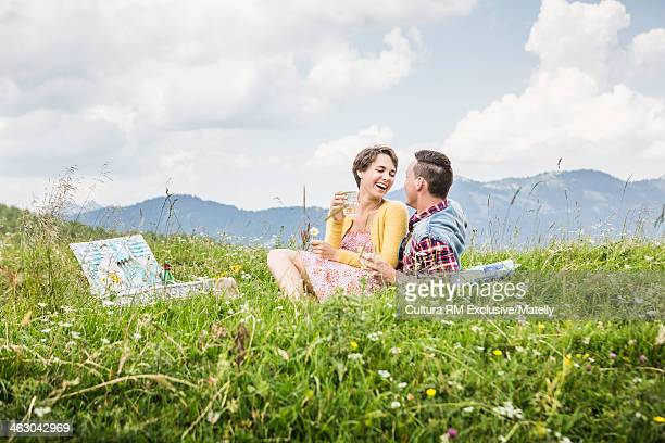 Young couple picnicing in meadow, Tyrol, Austria