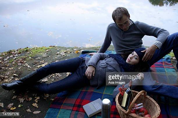 Young couple picnicking lakeside