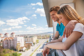 Young Couple Hugging And Enjoying The View From A Balcony