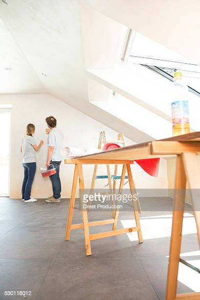 Young couple planning decorating new room