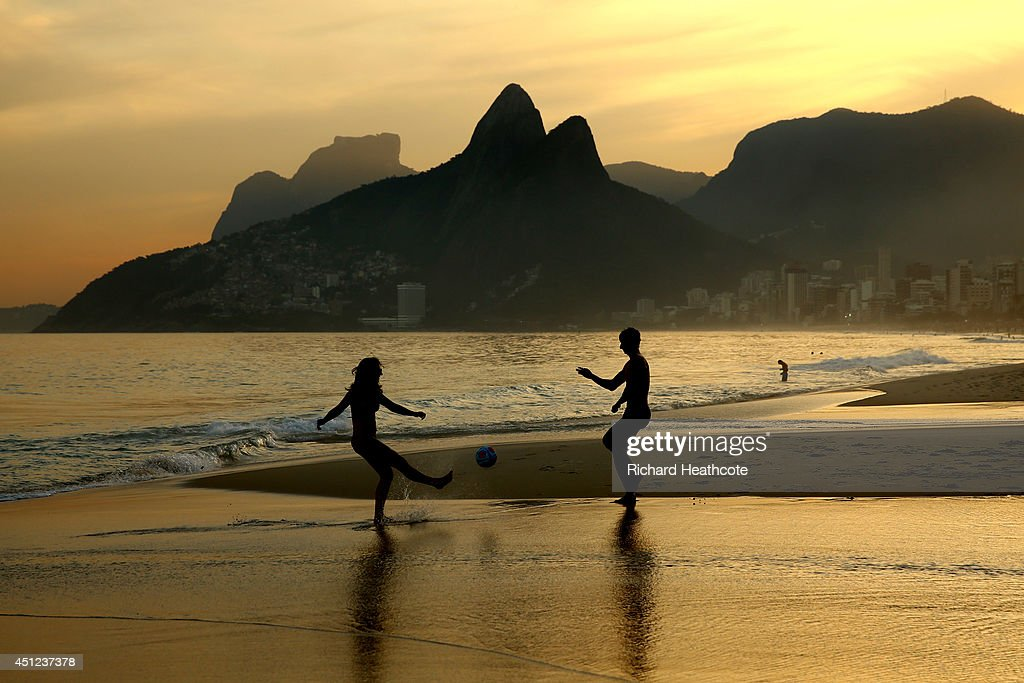 A young couple play football as the sunsets on Ipanema beach on June 25, 2014 in Rio de Janeiro, Brazil.