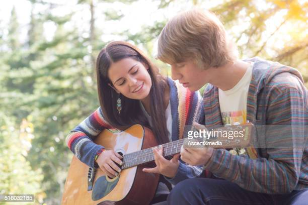 Young couple play guitar together, outdoors