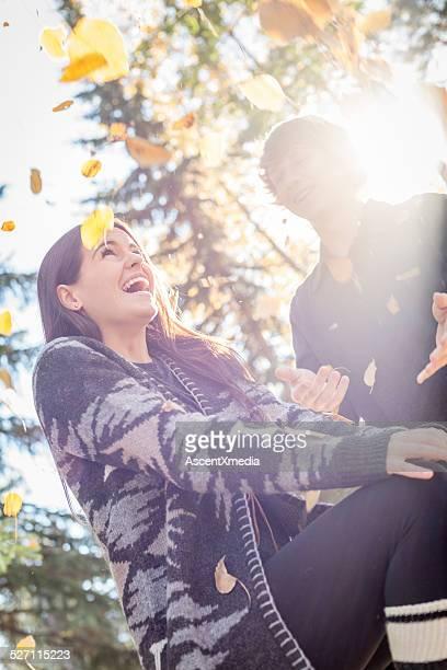 Giovane coppia divertirsi in autunno foglie, outdoors