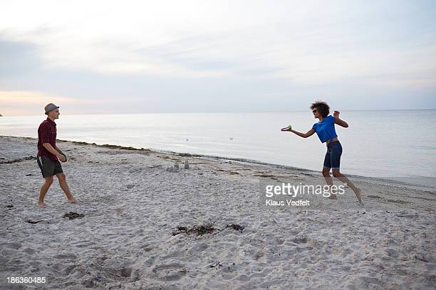 Young couple playing ball game on beach