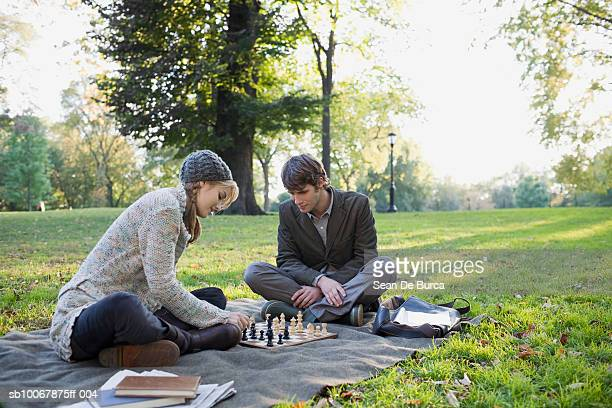 Young couple playing chess in park