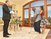 Young couple playing golf in a living room with a butler standing holding a tray with a glass of wine