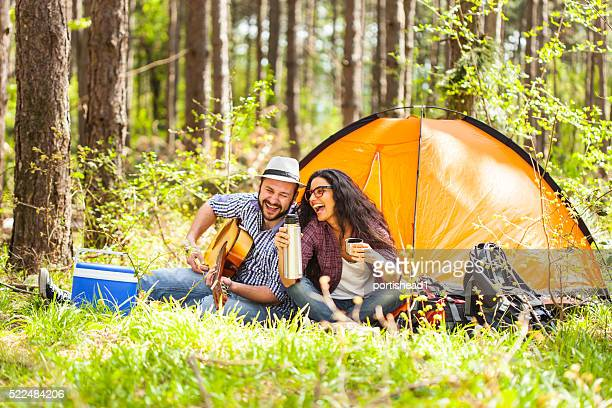 Young couple playing on guitar in the forest