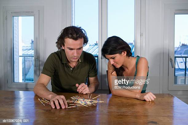 Young couple playing pick-up-sticks game, indoors