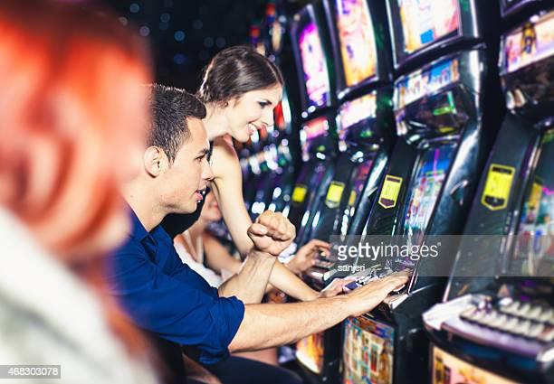 Pareja joven jugando máquinas tragamonedas en el Casino