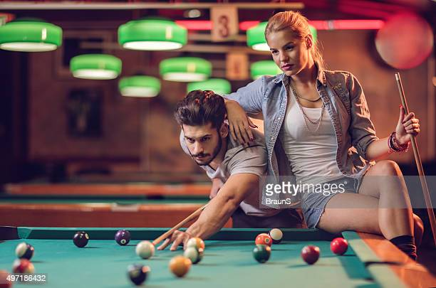 Young couple playing snooker in a pool hall.