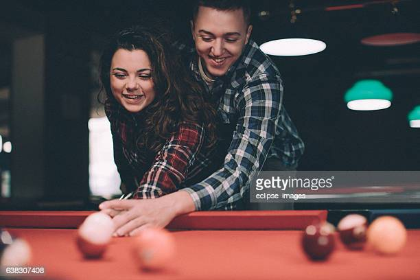 Young couple playing snooker in a pool hall