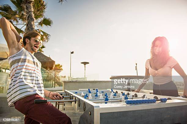 Young couple playing table football at San Diego beach