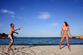 Young couple playing tennis on a beach during their vacation.