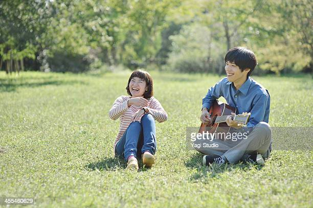 Young couple  playing the guitar in the green