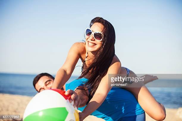 Jeune couple jouant au volley-ball sur la plage