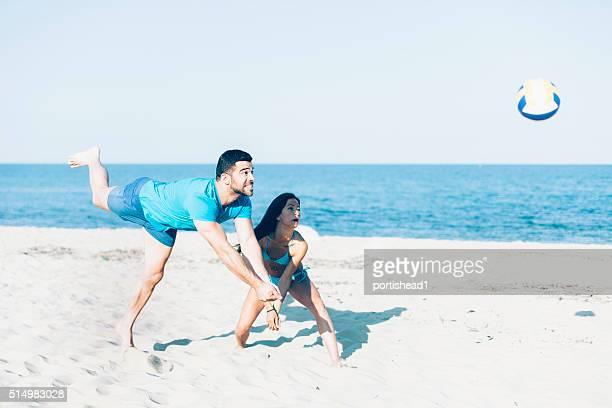Junges Paar spielen Sie volleyball am Strand.