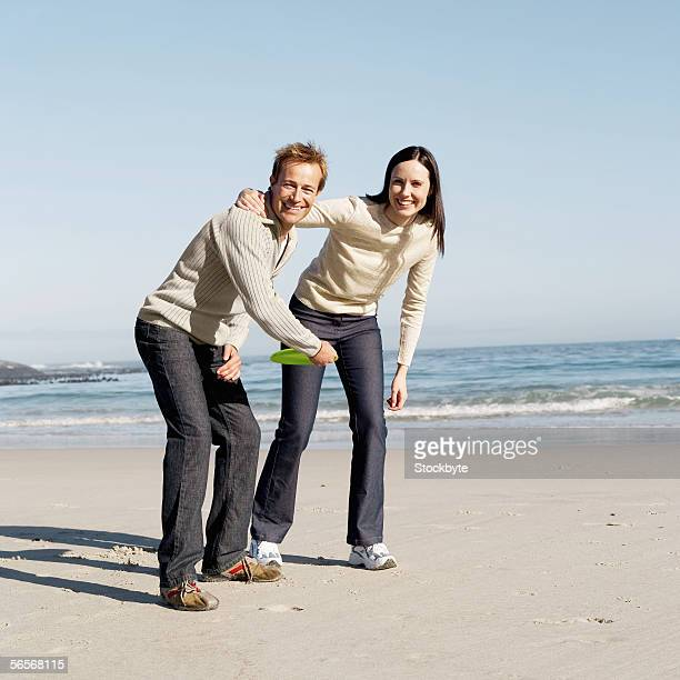 young couple playing with a flying disc on the beach