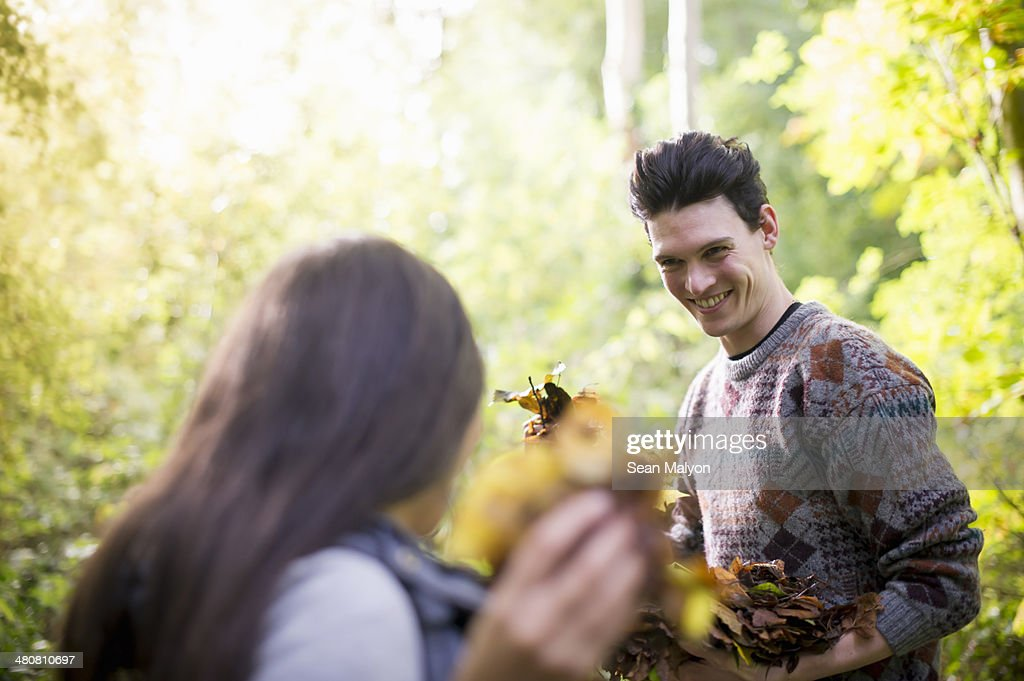 Young couple playing with autumn leaves in forest : Stock Photo