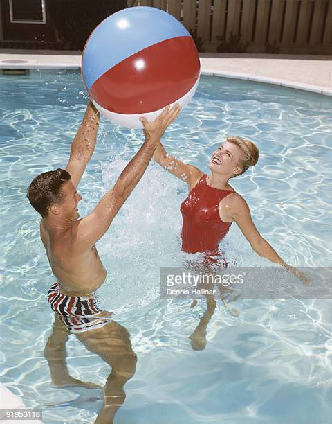 Young couple playing with beach ball in pool