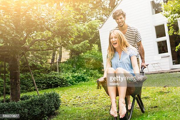 Young couple playing with wheel barrow in garden