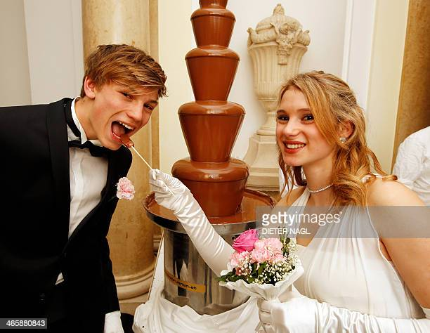 A young couple plays at a chocolate fountain during the opening of a traditional 'Zuckerbaeckerball' Ball of the Debutante at the Hofburg Palace on...