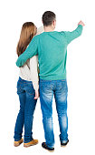 young couple pointing at wal Back view  (woman and man). Rear view people collection.  backside view of person.  Isolated over white background. Man and woman embracing each other to point the finger