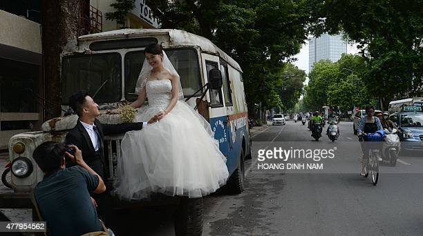 A young couple poses on an old Sovietera vehicle for their wedding photo album on a street in Hanoi on June 21 2015 AFP PHOTO / HOANG DINH Nam