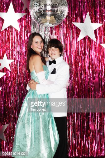 Young couple posing for photograph at formal dance, portrait