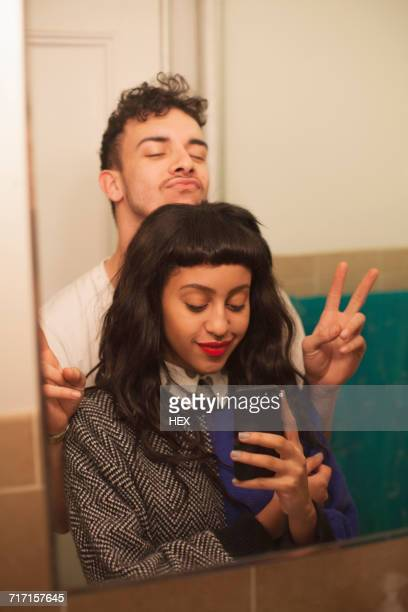Young couple posing for selfies in their bathroom
