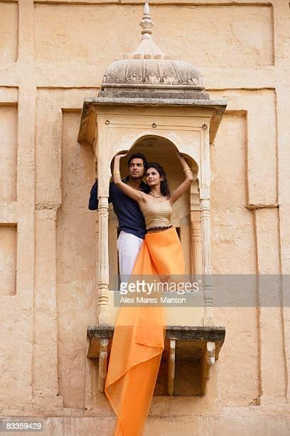 young couple posing on balcony