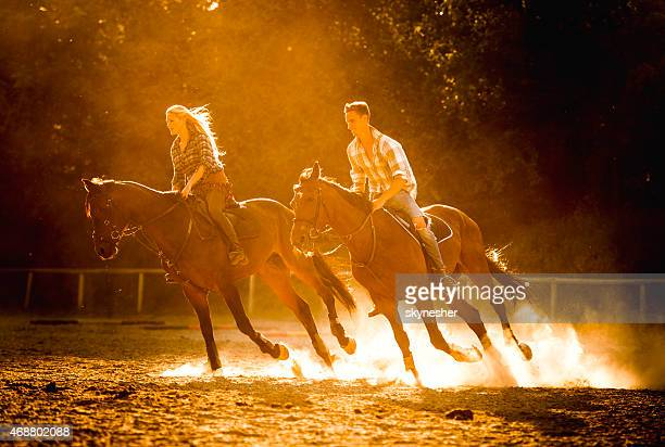 Young couple practicing with their horses at ranch.