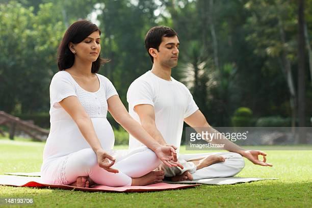 Jeune couple en pratiquant le yoga dans parc