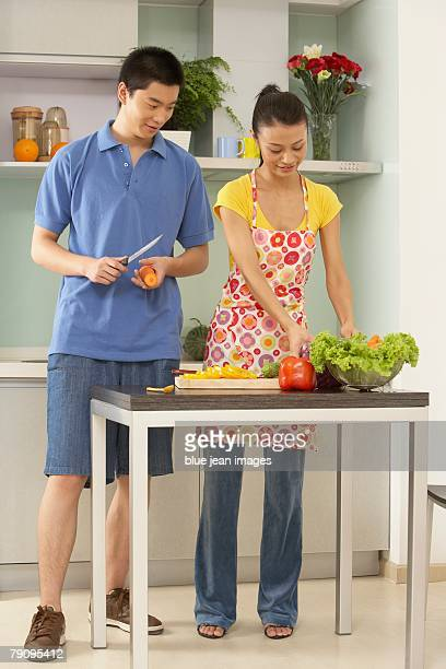 A young couple prepare vegetables in the kitchen.