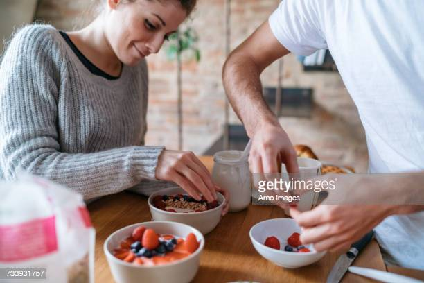 Young couple preparing breakfast together at kitchen counter