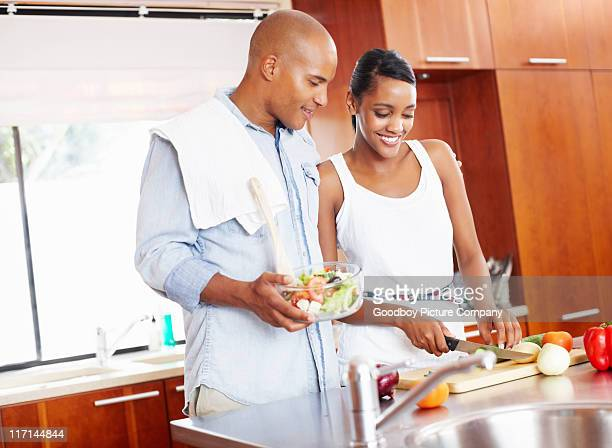 Young couple preparing fresh salad in kitchen