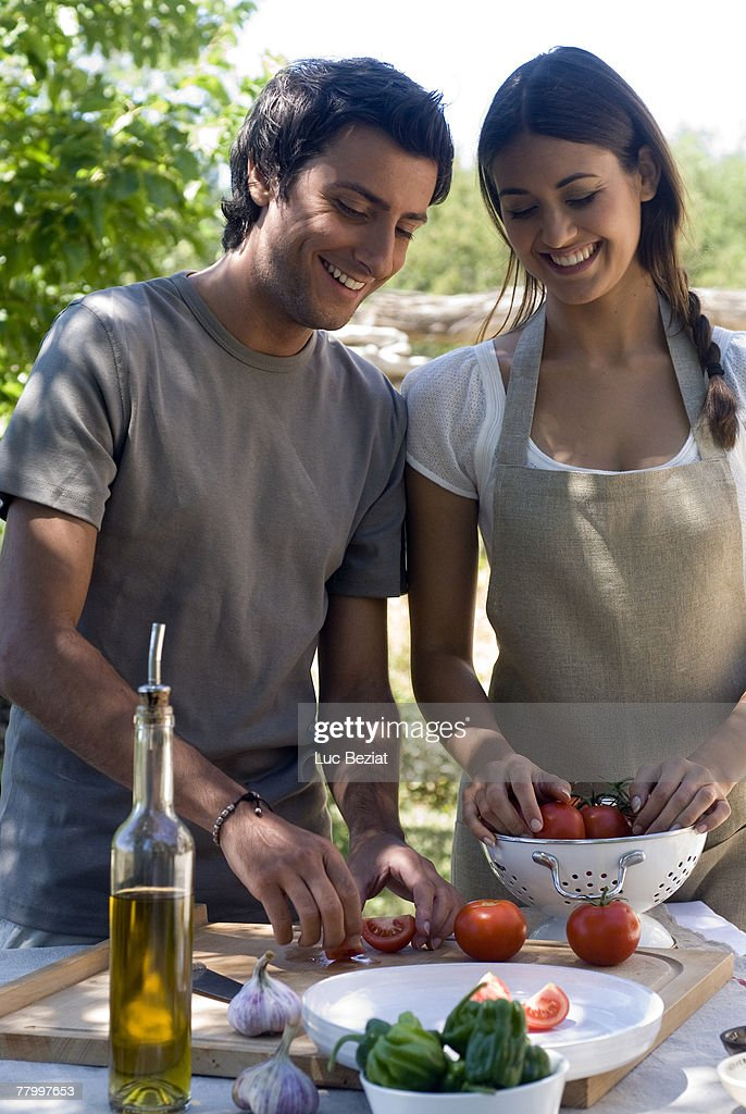 Young couple preparing fresh tomatoes