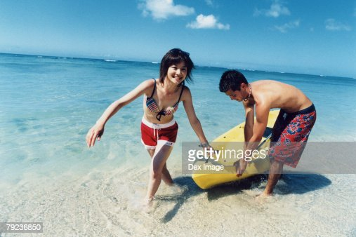 Young couple pulling kayak to shore : Stock Photo