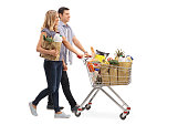 Full length profile shot of a young couple pushing a shopping cart full of groceries isolated on white background