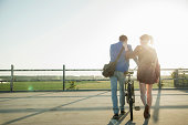 Young couple pushing bicycle in empty parking lot