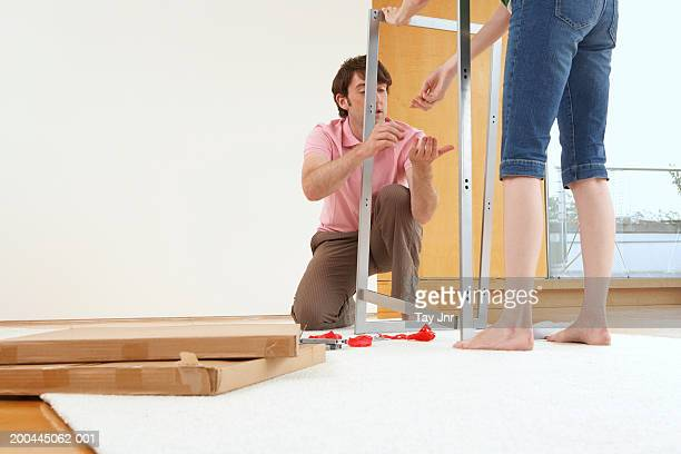 Young couple putting together flatpack furniture