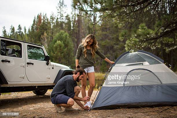 Young couple putting up tent in forest, Lake Tahoe, Nevada, USA