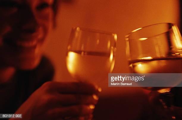 Young couple raising wine glasses, close-up (orange tone)